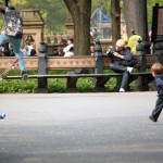 A skater and a kid chasing a ball